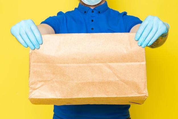 Joven repartidor en polo azul gorra azul jeans blancos mochila con cajas en amarillo