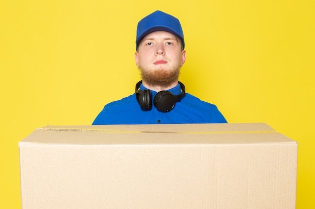 Joven repartidor en polo azul gorra azul jeans blancos mochila sosteniendo una caja en amarillo