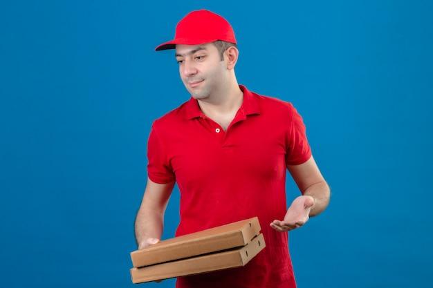 Joven repartidor en polo rojo y gorra con cajas de pizza mirando a un lado con cara inquisitiva sobre pared azul aislado