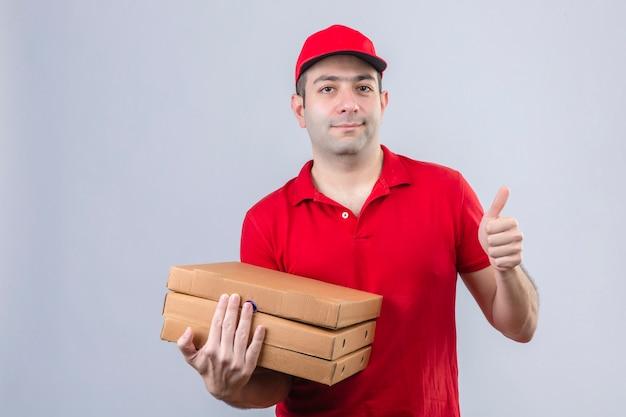 Joven repartidor en polo rojo y gorra con cajas de pizza sonriendo amable mostrando pulgar de pie sobre la pared blanca aislada