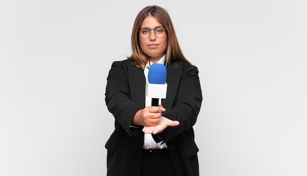 Joven reportera sonriendo felizmente con mirada amigable, segura y positiva, ofreciendo y mostrando un objeto o concepto
