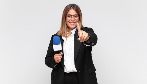 Joven reportera sonriendo con orgullo y confianza haciendo la pose número uno triunfalmente, sintiéndose como un líder