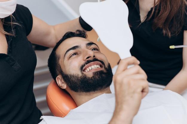 Joven revisando sus dientes en el espejo después del tratamiento dental - concepto de cuidado corporal y estomatología de personas para un estilo de vida saludable