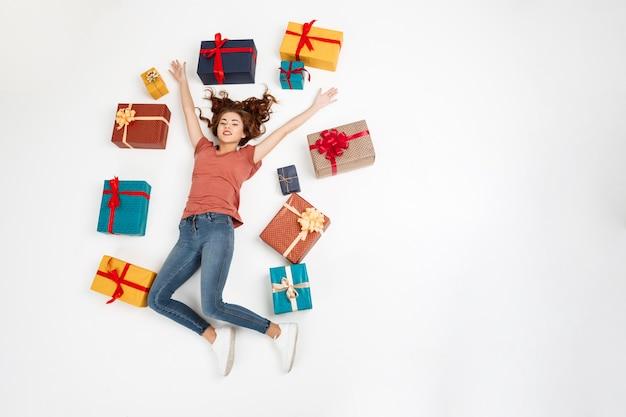 Joven rizada acostada entre cajas de regalo