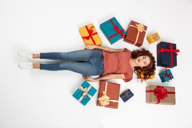 Joven rizada acostada en el piso entre cajas de regalo
