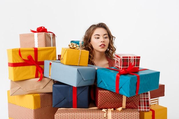 Joven rizada entre cajas de regalo
