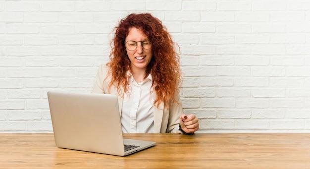 La joven rizada pelirroja que trabaja con su computadora portátil se ríe y cierra los ojos, se siente relajada y feliz