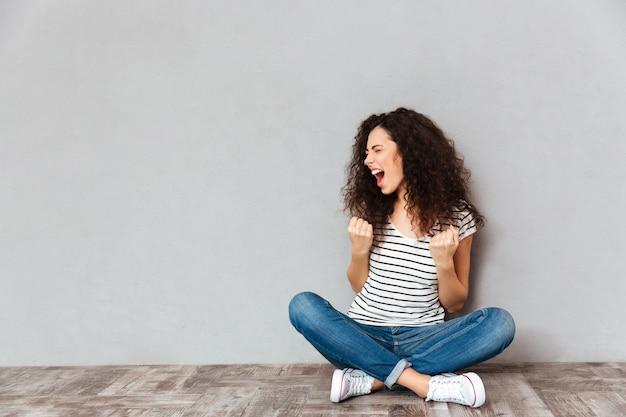 Joven rizada en ropa casual expresando deleite mientras está sentada en postura de loto en el suelo apretando los puños y gritando de alegría sobre la pared gris