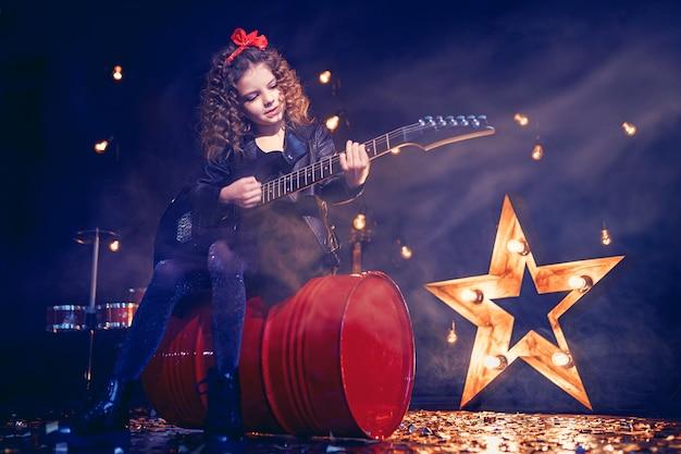 Joven rock niña tocando la guitarra eléctrica