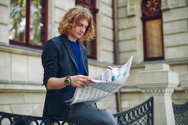 Joven rojizo leyendo periódico cerca de edificio de estilo antiguo