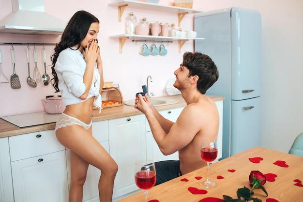 Joven romántico de pie sobre una rodilla en la cocina. él hace proposición a la mujer. ella se ve emocionada. decoración y copas de vino en la mesa.