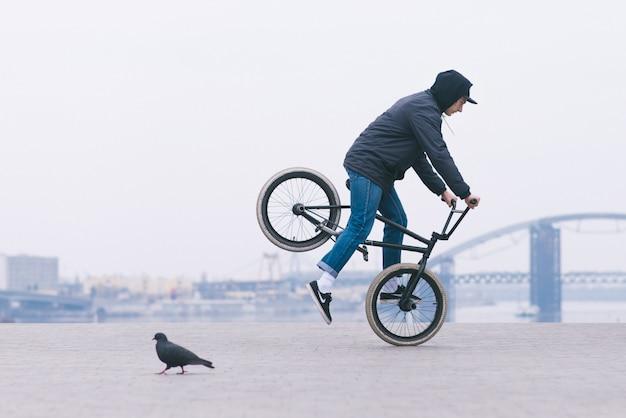Un joven en ropa casual monta en una rueda delantera de bicicleta bmx. trucos en bmx