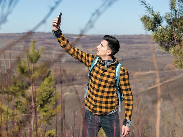 Joven en ropa casual perdido en la naturaleza tratando de atrapar la señal