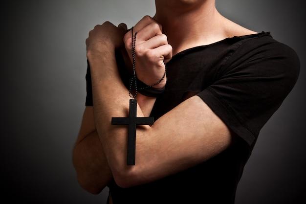 Joven en ropa negra moderna con gran cruz negra en las manos