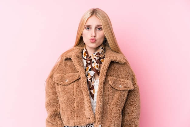 Joven rubia con un abrigo contra una pared rosada sopla mejillas, tiene expresión cansada. concepto de expresión facial