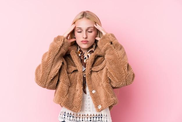 Joven rubia con un abrigo en rosa tocar templos y tener dolor de cabeza.