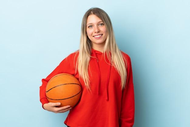 Joven rubia aislada en la pared azul jugando baloncesto