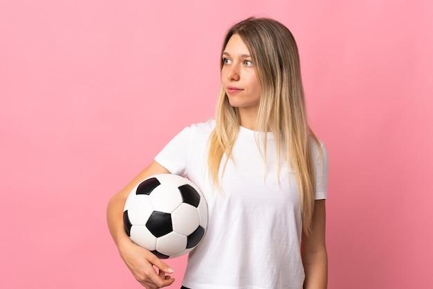 Joven rubia aislada en rosa con balón de fútbol