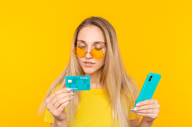 Joven rubia aoman sostiene una tarjeta de crédito y usa un teléfono inteligente en amarillo