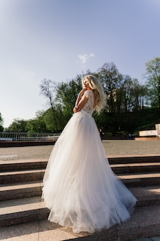 Joven rubia atractiva novia caminando en el parque