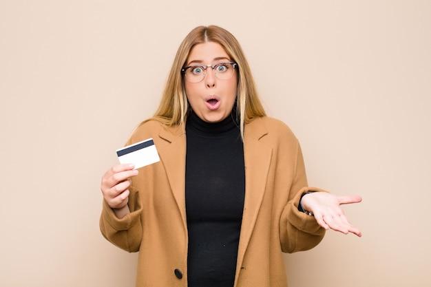 Joven rubia con la boca abierta y asombrada, sorprendida y asombrada con una increíble sorpresa con una tarjeta de crédito