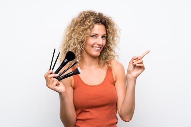 Joven rubia con cabello rizado sosteniendo una gran cantidad de pincel de maquillaje sorprendido y apuntando con el dedo hacia un lado