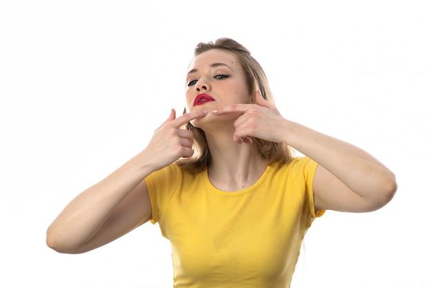 Joven rubia con camiseta amarilla limpiando su rostro
