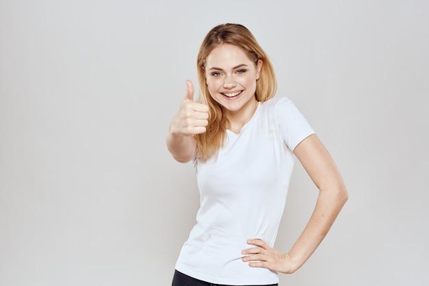 Joven rubia en una camiseta blanca posando