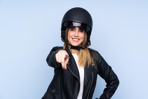 Joven rubia con un casco de moto y apuntando hacia el frente sobre una pared aislada