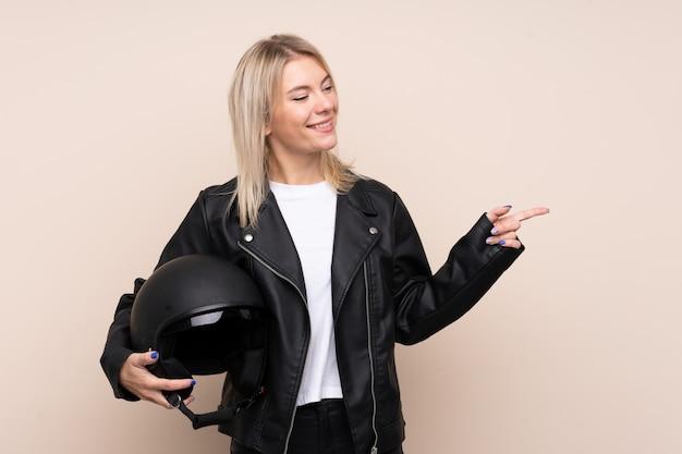 Joven rubia con un casco de moto apuntando hacia el lado