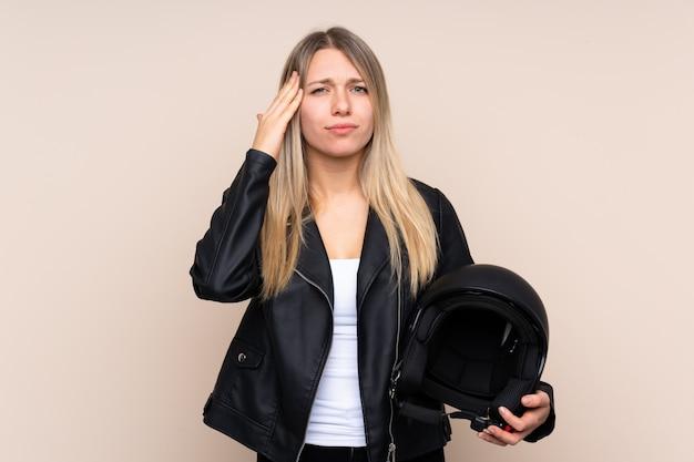 Joven rubia con un casco de moto infeliz y frustrado con algo. expresión facial negativa