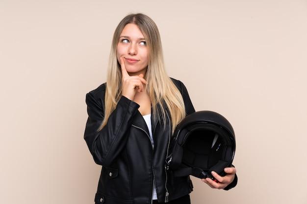 Joven rubia con un casco de moto pensando en una idea