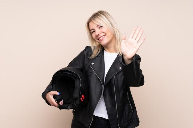 Joven rubia con un casco de moto sobre pared aislada saludando con la mano con expresión feliz
