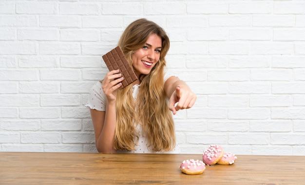 Joven rubia con chocolat apuntando al frente