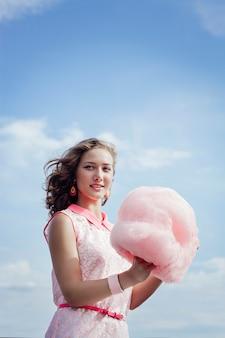 Joven rubia come algodón de azúcar en el verano