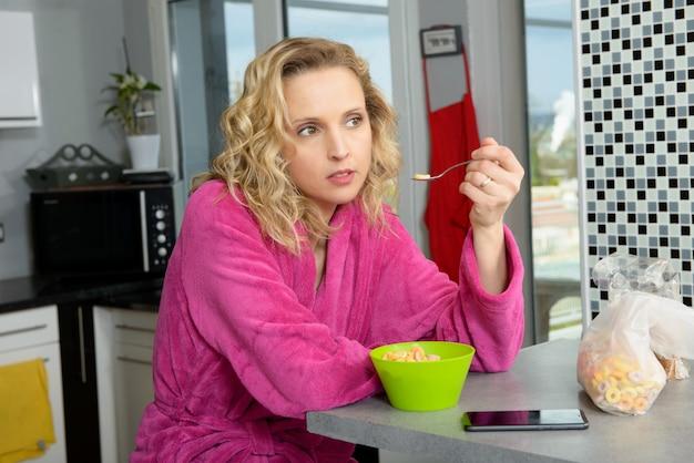 Joven rubia comiendo cereales en la mañana