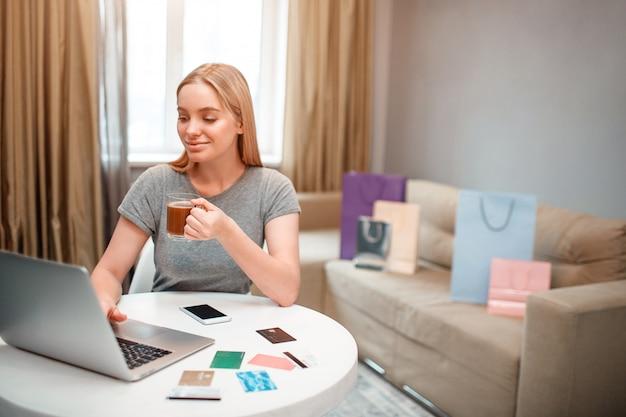 La joven rubia compradora de té está contenta con los grandes descuentos mientras está sentado a la mesa
