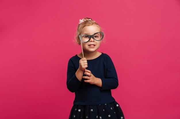 Joven rubia contenta con lentes de papel y mirando a la cámara sobre pared rosa