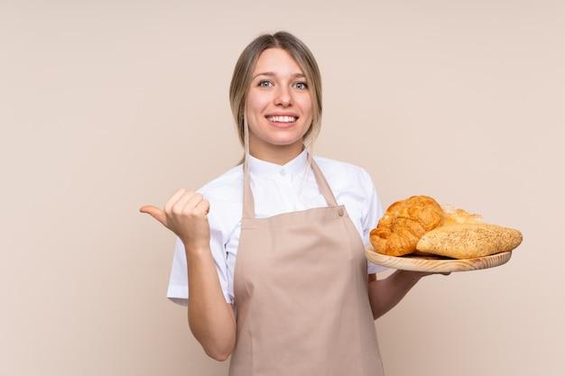 Joven rubia con delantal. mujer panadero sosteniendo una mesa con varios panes apuntando hacia un lado para presentar un producto