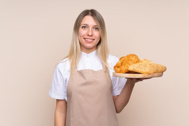 Joven rubia con delantal. panadero hembra sosteniendo una mesa con varios panes sonriendo mucho