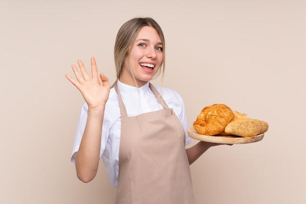 Joven rubia con delantal. panadero de sexo femenino que sostiene una tabla con varios panes saludando con la mano con expresión feliz