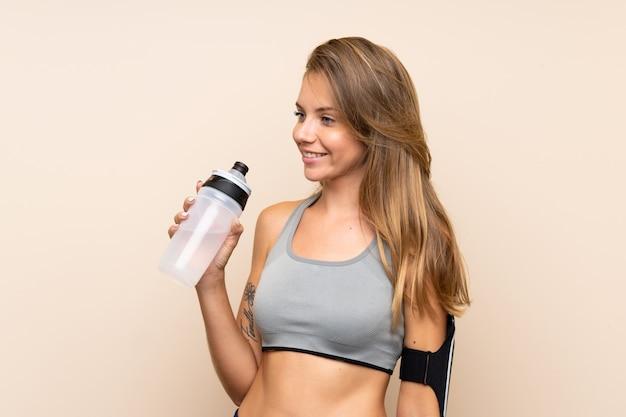 Joven rubia deporte chica sobre pared aislada con botella de agua deportiva