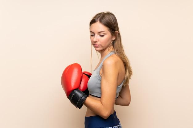 Joven rubia deporte chica sobre pared aislada con guantes de boxeo