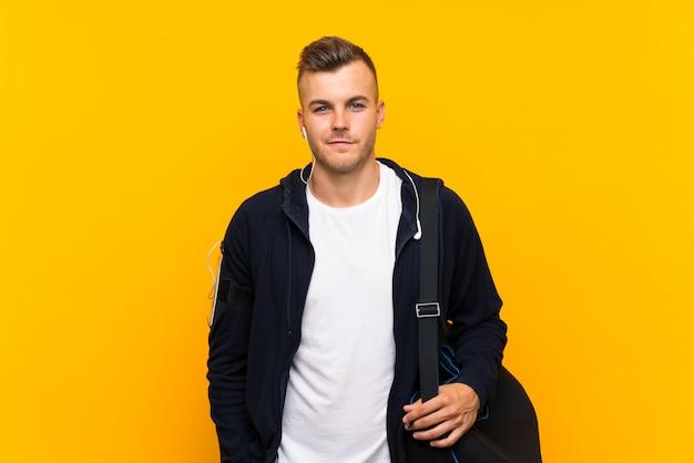 Joven rubia deporte hombre aislado pared amarilla sonriendo mucho