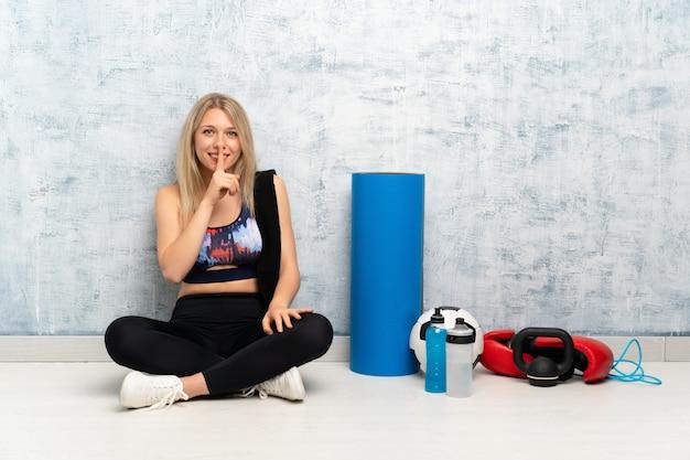 Joven rubia deporte mujer sentada en el suelo haciendo gesto de silencio