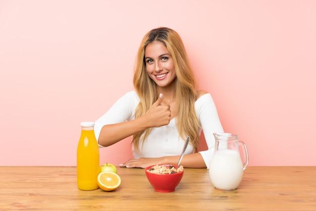 Joven rubia desayunando leche dando un gesto de pulgares arriba