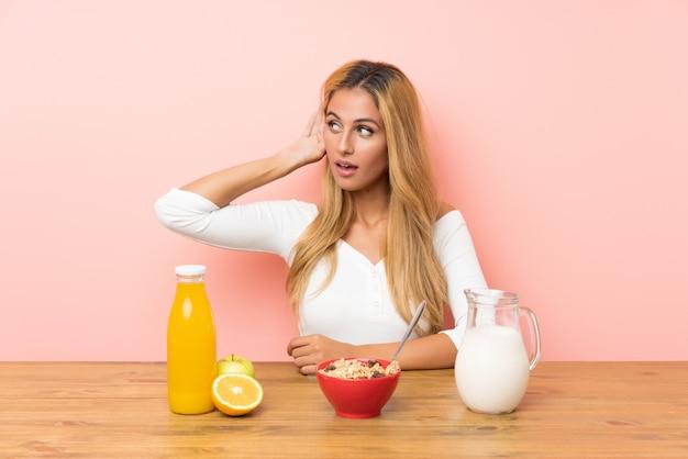 Joven rubia desayunando leche escuchando algo
