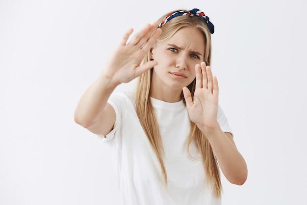 Joven rubia disgustada y molesta posando contra la pared blanca