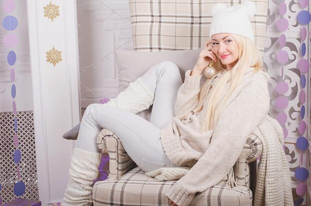 Joven rubia en un divertido sombrero sentado en una acogedora silla de navidad, emociones positivas y cálidas