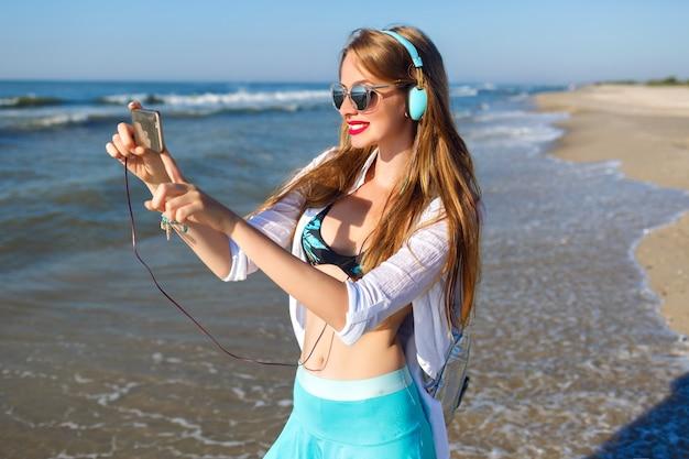 Joven rubia divirtiéndose en la playa, cierre de hipster brillante, vacaciones cerca del mar, escuchando música relajante y haciendo selfie en su teléfono.
